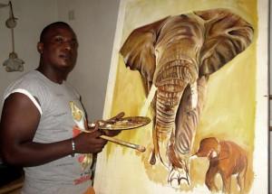 Der Maler Silas Malack bei der Arbeit am Bild mit Elefanten.